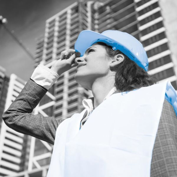 Female architect visiting construction site of high-riser
